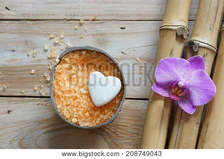 Spa set on wooden table coconut and bath salt flower of orchids and white stone in the shape of a heart natural bamboo