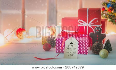 Christmas and New Year holidays gift box with decorative ornament on white wooden table with falling snow effect.Merry Christmas & Happy New Year 2018 paper tag.Gifts and congratulations concept.