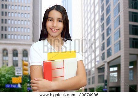 Brunette student young girl teen latin holding books modern city buildings