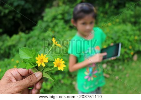 Asian children searching for flower species by tablet in the garden Learning biology plant outside the classroom.