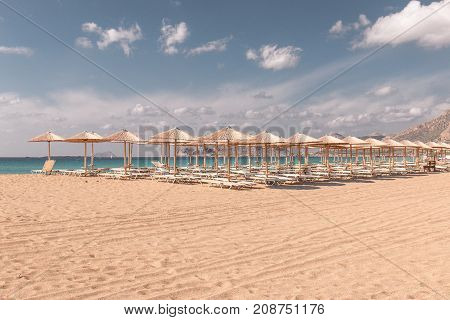 Beach sunbeds and parasols overlooking turquoise water