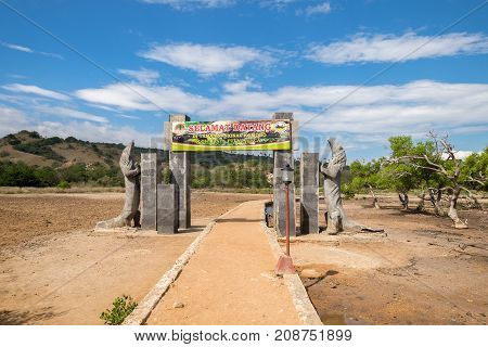 East Nusa Tenggara Indonesia - July 25 2017: The walkway is made of concrete with Komodo Dragon statue and sign to Komodo National Park on Rinca island Indonesia.