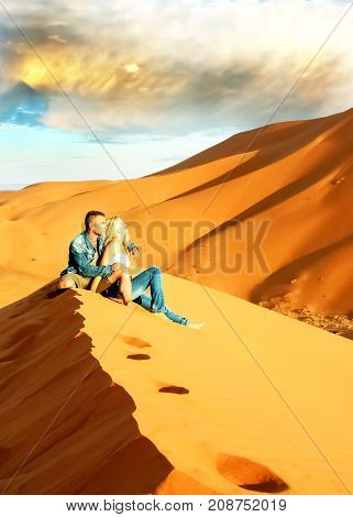 Young lovers in jeans clothes on sand dunes in the Sahara Desert.