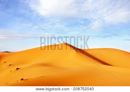 High sand dunes of the Sahara desert against a blue sky with clouds.
