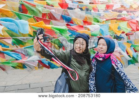 Mother and daughter tourists are traveling and selfie in Little Potala Palace Lamasery The famous temple in shangri-la yunnan china