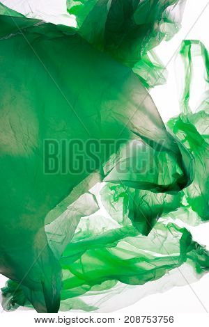 Crumpled green plastic bags isolated on white.