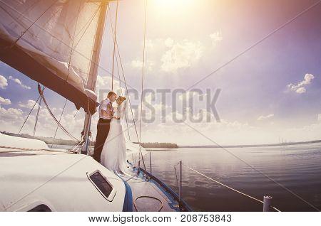 White Yacht With Sail Set Goes Along The Island On A Hot Day. Blue Sea, Blue Sky. Crimea. On Board A