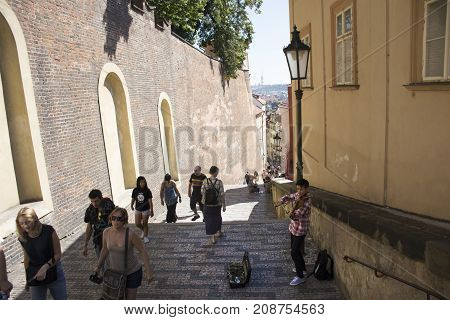 Czechia People Playing Violin For Money And Show With Travelers Walking Up And Down On Pathway Of Pr