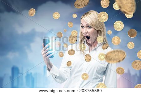 Portrait of an astonished blonde businesswoman holding a smartphone and looking at it in disbelief. There are bitcoins falling around her and a cityscape background. Toned image double exposure