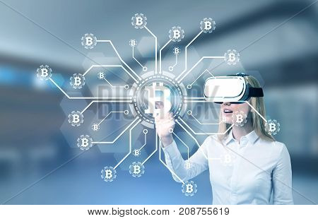 Blonde businesswoman wearing a white blouse and VR glasses is interacting with a bitcoin hologram in a modern office. Double exposure mock up