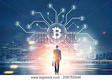 Rear view of a young businessman holding a suitcase looking at a bitcoin network hologram in a night city sky. Toned image double exposure.