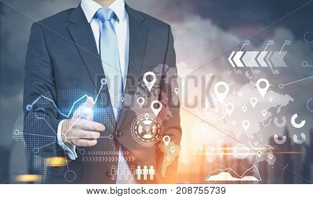Unrecognizable businessman with a glowing finger is interacting with an infographics hologram. A gray city background. Toned image double exposure
