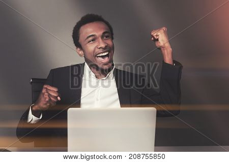 Happy African American businessman is sitting at his laptop in an office and celebrating sealing a good deal. Toned image mock up