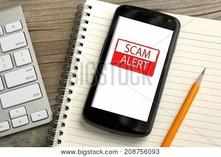 mobile phone showing scam alert warning with desk background