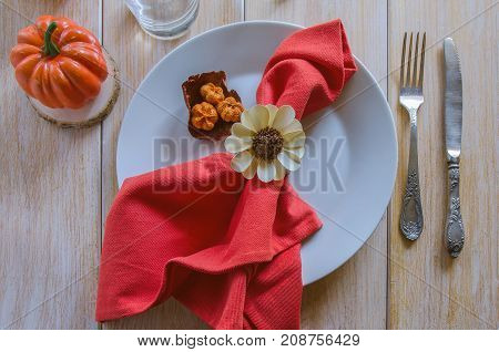Thanksgivings Day festive background. Beautiful autumn table settings for thanksgiving dinner: white plate with small pumpkin and orange linen napkin with vintage cutlery. Top view.