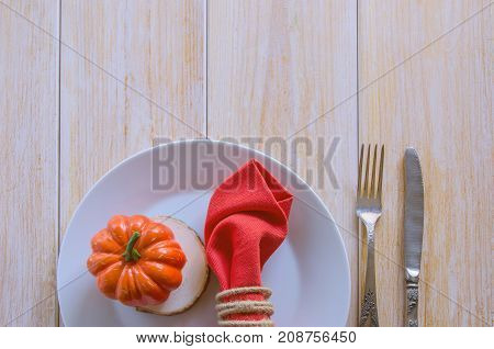 Thanksgivings Day festive background with copy space. Beautiful autumn table settings for thanksgiving dinner: white plate with small pumpkin and orange linen napkin with vintage cutlery. Top view.