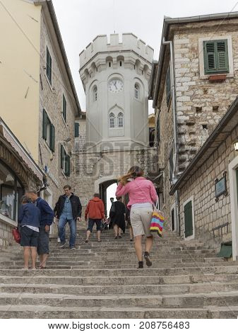 Herceg Novi - September 25 2017: People and tourists climb the steep staircase to the old gates of the city and the Sakhat Kula tower with the clock September 25 2017 Herceg Novi Montenegro