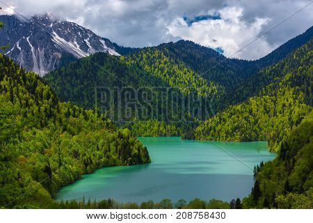 Mountain lake surrounded by green forests on the slopes incredible beauty against a background of melting snow on top. Ritsa lake, Relict national park of Ritsa, Abkhazia.