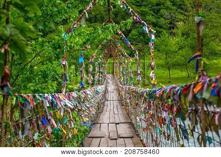 A pedestrian suspension bridge across the river in Abkhazia. Multicolored ribbons are hung on it. Suspension bridge in Abkhazia.