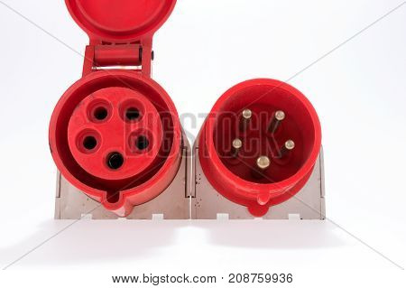 Red and white three-phase plug and socket with a lid lying beside isolated on white