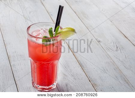 Red Cocktail with ice and lime on white wooden background .