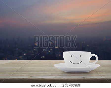 White coffee cup with smile face shape on wooden table over blur modern city tower on warm light sundown Good morning concept
