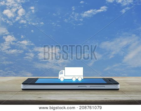 Truck flat icon on modern smart phone screen on wooden table over blue sky with white clouds Business transportation service concept