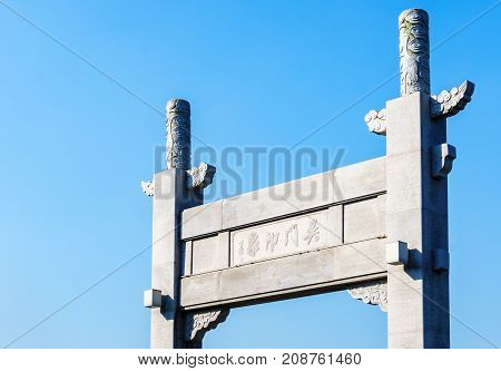 Suzhou, China - Nov 5, 2016: Closeup of stone gate in classical Chinese design named Wumen Impression (Chinese characters) on a public park, along the Waicheng River.