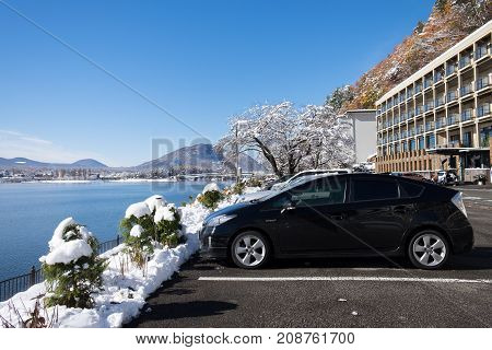 Yamanashi Japan - November 25 2016: Car park around Lake Kawaguchi with autumn forest after snowfall during sunset in the winter at Japan