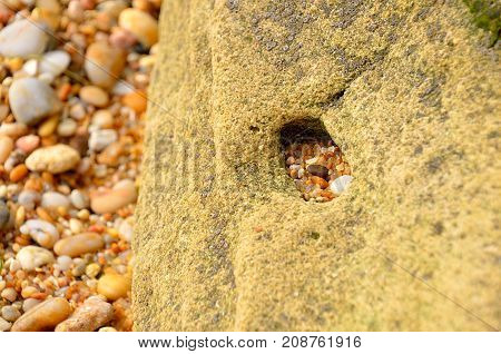 Stone hole. Small stones and sand crumbs in the large rock cavity.