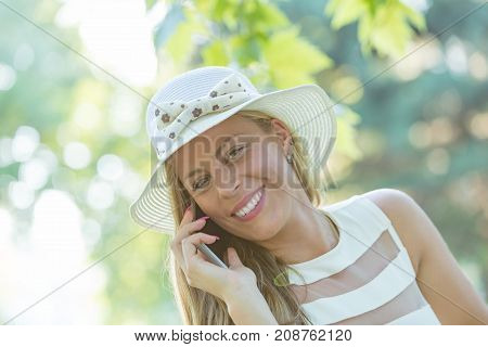 Cute girl using cellphone in the nature.