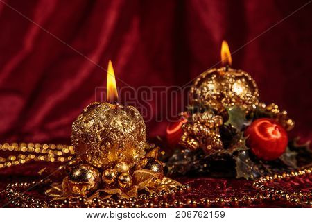 Christmas still life with two spherical candles on Burgundy background