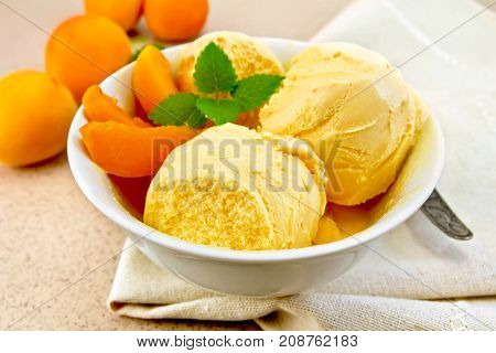 Apricot ice cream in a white bowl with slices of fruit, spoon on a napkin on a background granite table