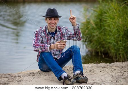 Young smiling man in fashionable clothes sits on the river bank with a phone and listens to music on headphones