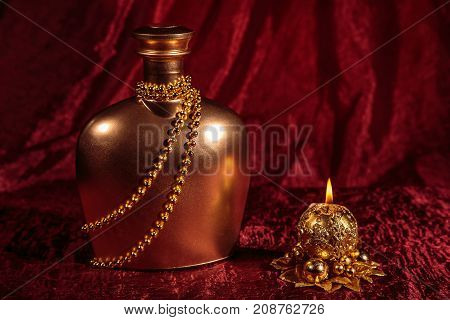 A bottle of brandy and candle in New year and Christmas on red background