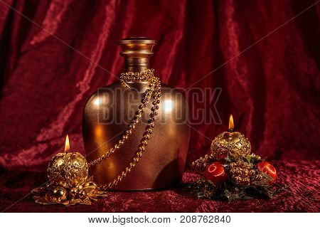 A bottle of brandy and two candles in New year and Christmas on red background