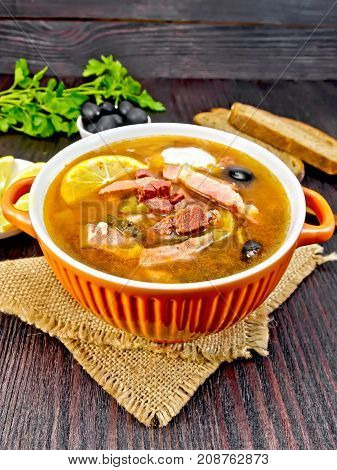 Soup saltwort with lemon, meat, pickles, tomato sauce and olives in a sackcloth, bread, parsley and spoon on a background of a dark wooden board