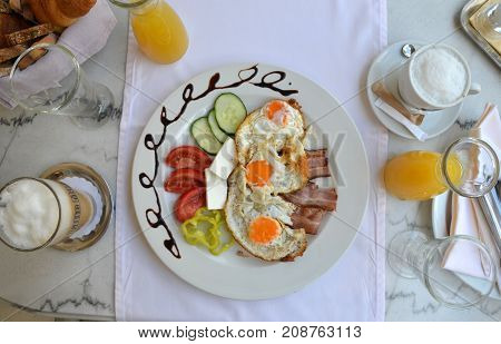 Decorated plate with served breakfast - fried eggs bacon and fresh vegetables