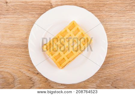 One Waffle In White Plate On Wooden Table