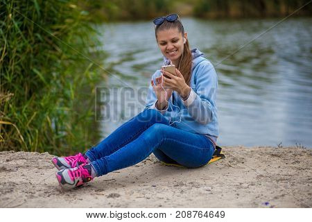 Young woman in excellent spirits sits on the river bank with a phone and listens to music
