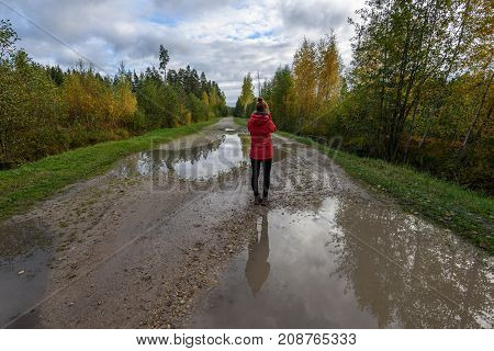 Young Woman In Red Jacket Enjoying Nature On Dirt Road. Latvia