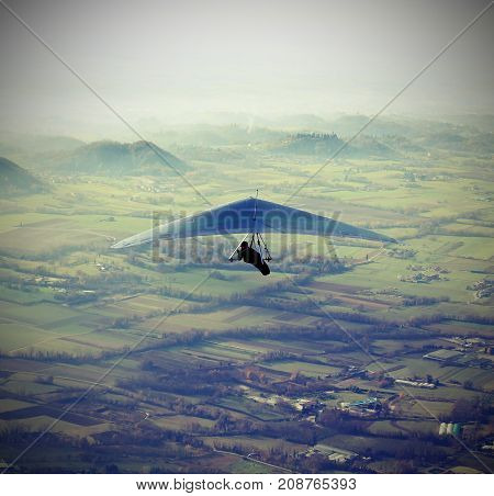 man flying high with his hang glider above the plain with vintage effect