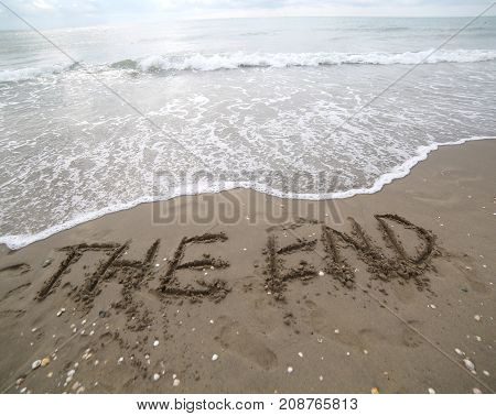 The End Text Written On The Sand And The Wave That Is Deleting T