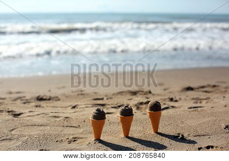 Three Ice Cream Cones Stuffed With Wet Sand To Play On The Beach
