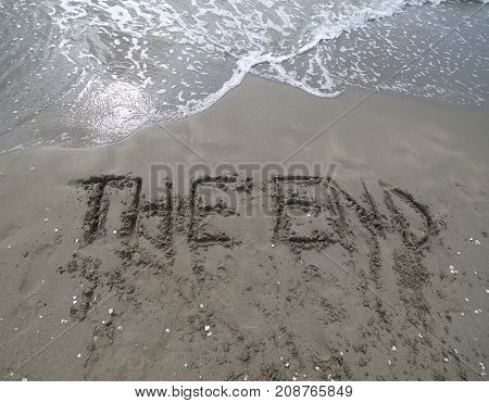 Text The End Written On The Sand And The Wave That Is Deleting T