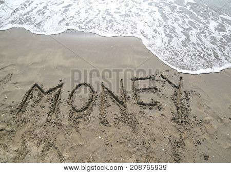 Word Money Written On The Sand And The Wave That Is Erasing The