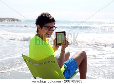 Young Smiling Caucasian Boy Reads A Technological E-book On The
