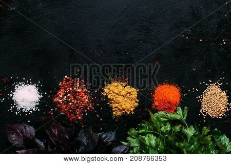 food spice salt mustard pepper paprika tumeric parsley basil dark background concept