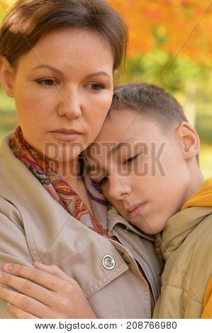 portrait of sad mother and son outdoors