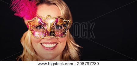 Portrait of happy woman in masquerade mask against black background